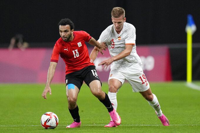 Egypt's Karim Eraky, left, and Spain's Dani Olmo battle for the ball during a men's soccer match at the 2020 Summer Olympics, Thursday, July 22, 2021, in Sapporo, Japan. (AP Photo/SIlvia Izquierdo)