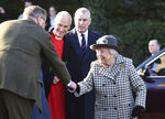 Britain's Queen Elizabeth II, right, arrives at St Mary the Virgin, in Hillington, England, to attend a Sunday church service, Sunday, Jan. 19, 2020. Buckingham Palace says Prince Harry and his wife, Meghan, will no longer use the titles