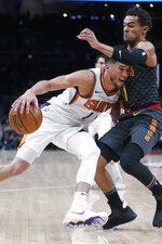Phoenix Suns guard Devin Booker (1) drives against Atlanta Hawks guard Trae Young (11) in the first half of an NBA basketball game Tuesday, Jan. 14, 2020, in Atlanta. (AP Photo/John Bazemore)