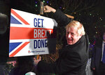 Britain's Prime Minister and Conservative party leader Boris Johnson poses as he hammers a