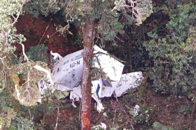 In this photo released by Indonesia's National Search and Rescue Agency (BASARNAS), the wreckage of a small Rimbun Air cargo airplane is seen from a rescue helicopter in the mountain near Intan Jaya, Papua province, Indonesia, Wednesday, Sept. 15, 2021. The plane was reported missing 50 minutes after it took off Wednesday in the country's easternmost province. (BASARNAS via AP)