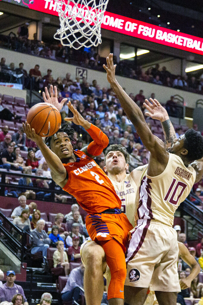 Clemson gurnard al-Amir Dawes (2) shoots between Florida State forward Malik Osborne (10) and center Dominik Olejniczak (15) in the first half of an NCAA college basketball game in Tallahassee, Fla., Sunday, Dec. 8, 2019. (AP Photo/Mark Wallheiser)