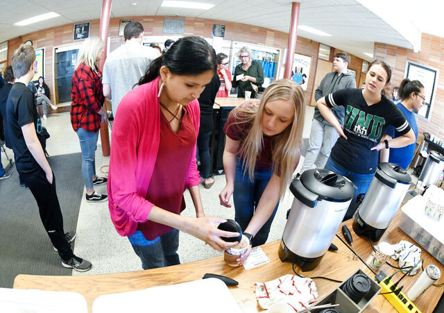 Mandan (North Dakota) High School student Sheridan Two Bears, left, makes a cup of hot chocolate with the help of Kendra Gerving, a University of Mary student teacher, while working at the Braves Bean Coffee Shop inside the high school entrance on March 6, 2020. To the right is Amanda Zeller, a paraprofessional at the school, who also helps in the work experience class.  (Mike McCleary/The Bismarck Tribune via AP)
