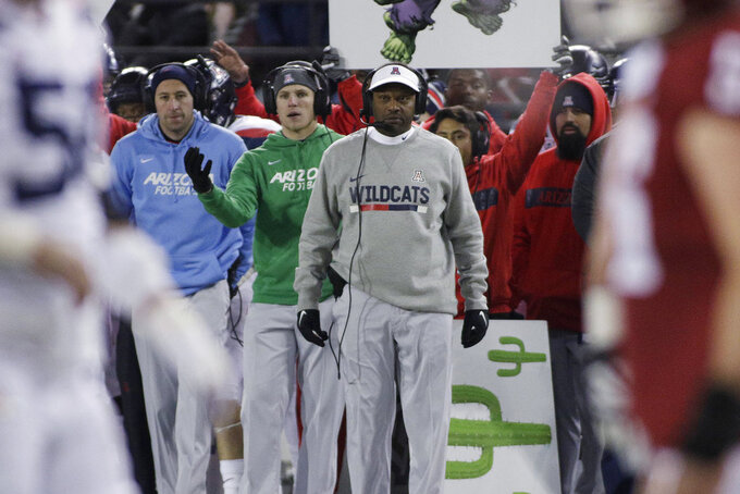 Arizona coach Kevin Sumlin, center in gray sweater, watches during the first half of the team's NCAA college football game against Washington State in Pullman, Wash., Saturday, Nov. 17, 2018. (AP Photo/Young Kwak)