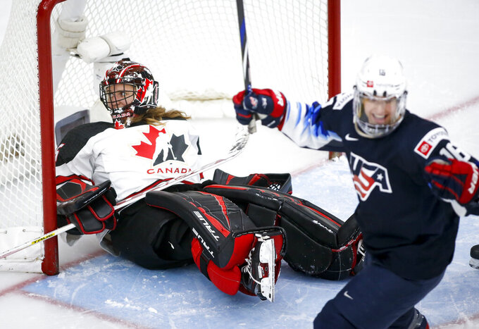 Canada's goalie Ann-Renee Desbiens, left, reacts after letting in a goal as United States' Jesse Compher celebrates during the third period of an IIHF women's world hockey championships game Thursday, Aug. 26, 2021, in Calgary, Alberta. (Jeff McIntosh/The Canadian Press via AP)