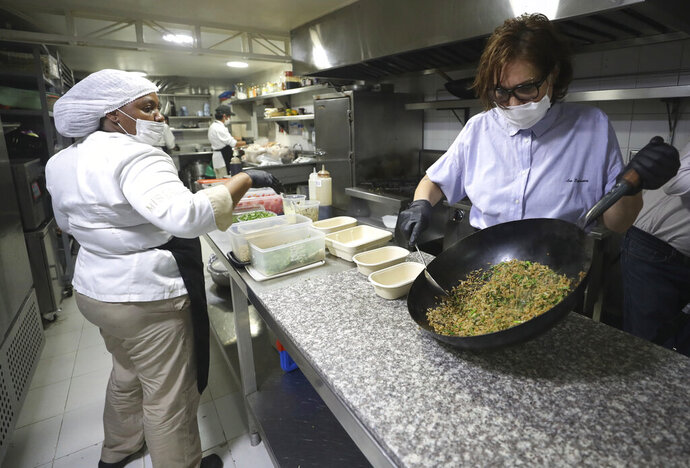 In this June 13, 2020 photo, chef Leonor Espinosa stirs a rice dish in the kitchen of Leo's restaurant, in Bogota, Colombia. Facing the new coronavirus pandemic Espinosa said,