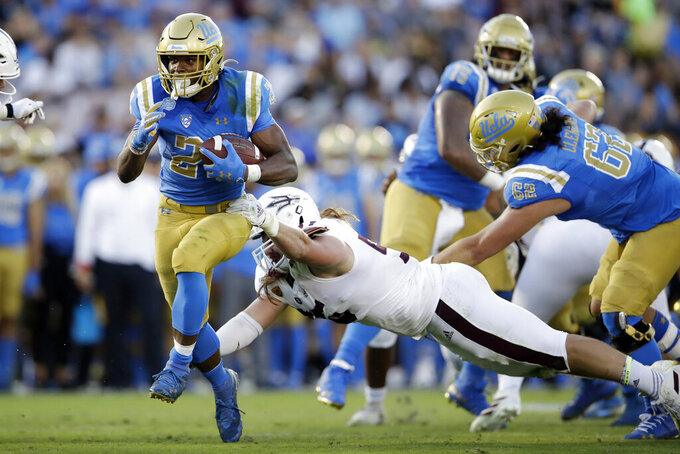 UCLA running back Joshua Kelley, left, runs for a touchdown past Arizona State defensive lineman Roe Wilkins during the first half of an NCAA college football game Saturday, Oct. 26, 2019, in Pasadena, Calif. (AP Photo/Marcio Jose Sanchez)
