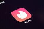 FILE - This Tuesday, July 28, 2020, file photo shows the icon for the Tinder dating app on a device in New York. The use of dating apps in the last 18 months of the pandemic has surged around the globe. Tinder reported 2020 as its busiest year. (AP Photo/Patrick Sison, File)