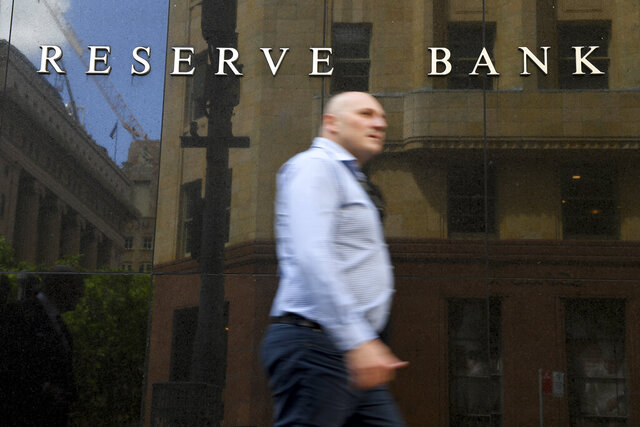 A man walks past the Reserve Bank of Australia headquarters in Sydney, Tuesday, Nov. 3, 2020. Australia's central bank on Tuesday cut its benchmark interest rate by 0.15 of a percentage point to a record low 0.10% in a bid to lift the economy from a pandemic-induced recession.(Dan Himbrechts/AAP Image)