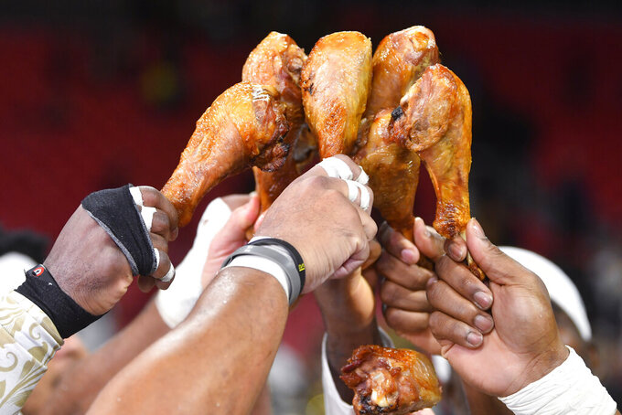 New Orleans Saints players toast drumsticks after an NFL football game against the Atlanta Falcons, Thursday, Nov. 28, 2019, in Atlanta. The New Orleans Saints won 26-18. (AP Photo/John Amis)