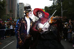 A couple dressed as Catrinas parade down Mexico City's iconic Reforma avenue during celebrations for the Day of the Dead in Mexico, City, Saturday, Oct. 26, 2019. (AP Photo/Ginnette Riquelme)