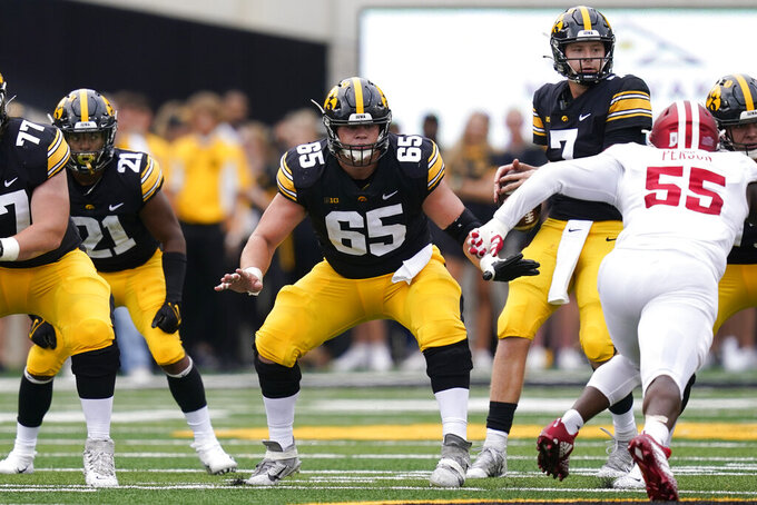 FILE - Iowa offensive lineman Tyler Linderbaum (65) looks to make a block during the first half of an NCAA college football game against Indiana in Iowa City, Iowa, in this Saturday, Sept. 4, 2021, file photo. Lindenbaum was selected to The Associated Press Midseason All-America team, announced Tuesday, Oct. 19, 2021. (AP Photo/Charlie Neibergall, File)