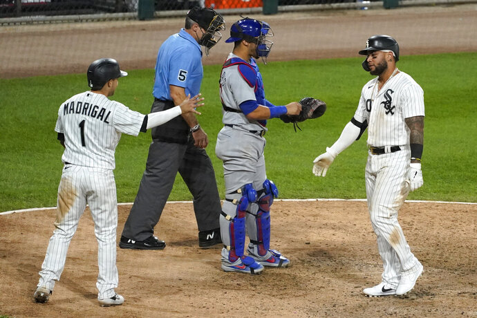 Chicago White Sox's Yoan Moncada, right, is congratulated by Nick Madrigal after hitting a two-run home run during the sixth inning of the team's baseball game against the Chicago Cubs in Chicago, Saturday, Sept. 26, 2020. (AP Photo/Nam Y. Huh)