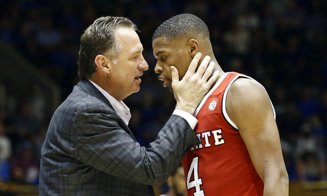 FILE - In this Jan. 23, 2017, file photo, N.C. State's head coach Mark Gottfried speaks with Dennis Smith Jr. during the second half of an NCAA college basketball game in Durham, N.C. North Carolina State's NCAA case involving recruiting violations tied to former Wolfpack one-and-done star Smith Jr. has been recommended to go through an independent investigation process created for complex cases. Gottfried is charged individually in N.C. State's infractions case under the provision of head-coach responsibility for violations within his program. (AP Photo/Gerry Broome, File)