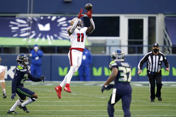 San Francisco 49ers wide receiver Brandon Aiyuk (11) makes a leaping catch against the Seattle Seahawks during the second half of an NFL football game, Sunday, Nov. 1, 2020, in Seattle. (AP Photo/Elaine Thompson)
