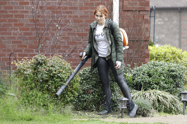 In this March 25, 2020, photo, country singer Caylee Hammack uses a leaf blower to clear a sidewalk as she does landscaping work in Mt. Juliet, Tenn. Hammack's band was facing months without income after their touring schedule was wiped clean due to the spreading coronavirus, so they started a side gig landscaping to keep bills paid. (AP Photo/Mark Humphrey)