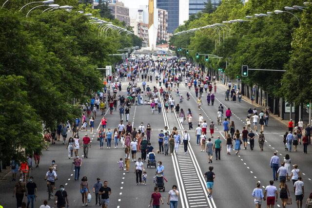 Families with their children play along the Paseo de la Castellana in Madrid, Spain, Saturday, May 30, 2020. Spanish authorities are reporting no setbacks in their gradual easing of restrictions on movement over this past month, as some regions prepare to further loosen limits from June 1. (AP Photo/Manu Fernandez)