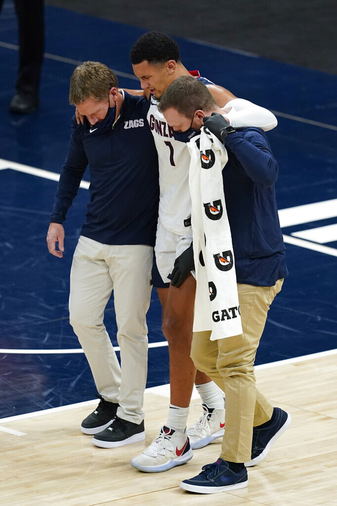 Gonzaga coach Mark Few, left, helps Jalen Suggs (1) off the court during the first half of the team's NCAA college basketball game against West Virginia, Wednesday, Dec. 2, 2020, in Indianapolis. (AP Photo/Darron Cummings)
