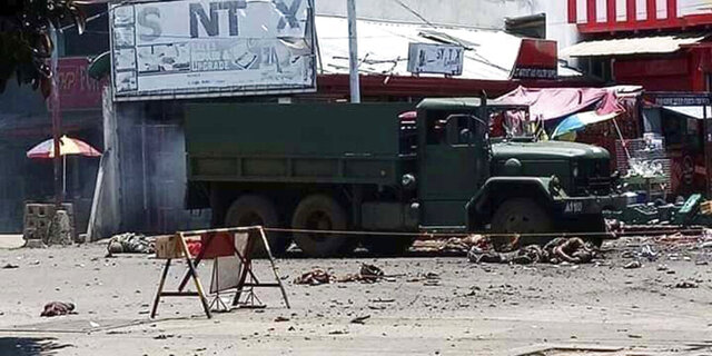 EDS NOTE: GRAPHIC CONTENT - In this photo provided by the Philippine Red Cross, a military truck lies at an area where a bomb exploded at the town of Jolo, Sulu province, southern Philippines, Monday, Aug. 24, 2020. Bombs exploded in the southern Philippine town Monday, killing several soldiers and wounding other military personnel and civilians despite extra tight security because of threats from Abu Sayyaf militants. (Philippine National Red Cross via AP)