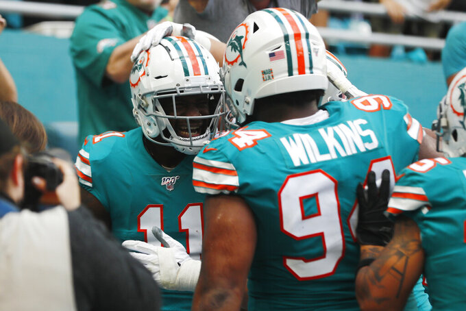 Miami Dolphins defensive tackle Christian Wilkins (94) congratulates wide receiver DeVante Parker (11), after Parker scored a touchdown, during the first half at an NFL football game against the Philadelphia Eagles, Sunday, Dec. 1, 2019, in Miami Gardens, Fla. (AP Photo/Brynn Anderson)