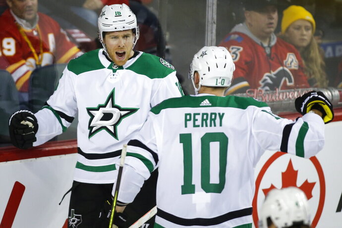 Dallas Stars' Joe Pavelski, left, celebrates his goal against the Calgary Flames with teammate Corey Perry during the second period of an NHL hockey game Wednesday, Nov. 13, 2019, in Calgary, Alberta. (Jeff McIntosh/The Canadian Press via AP)