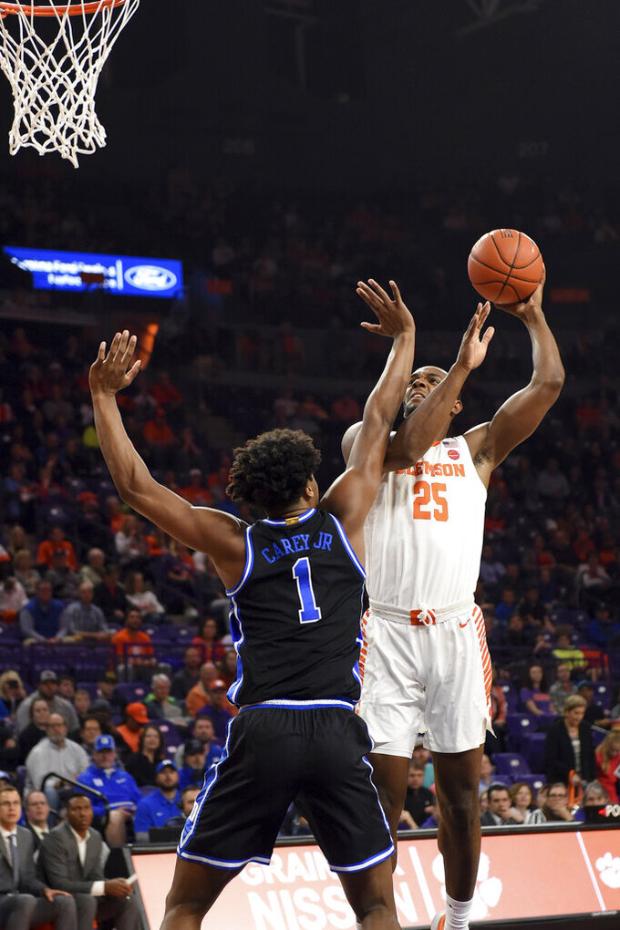 Clemson's Aamir Simms (25) shoots while defended by Duke's Vernon Carey Jr. during the first half of an NCAA college basketball game Tuesday, Jan. 14, 2020, in Clemson, S.C. (AP Photo/Richard Shiro)