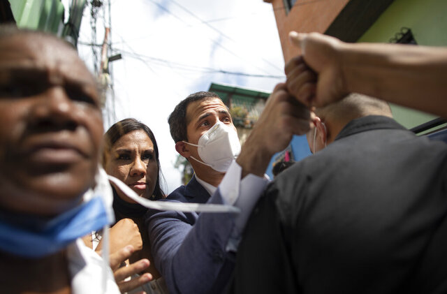 Venezuelan opposition leader Juan Guaidó fist bumps with a resident during a visit to La Lucha neighborhood of Caracas, Venezuela, Thursday, Dec. 10, 2020. Guaidó's coalition is holding a referendum which culminates on Saturday. It asks Venezuelans at home and abroad to say whether they wish to end President Nicolas Maduro's rule and hold fresh presidential and legislative elections. (AP Photo/Ariana Cubillos)