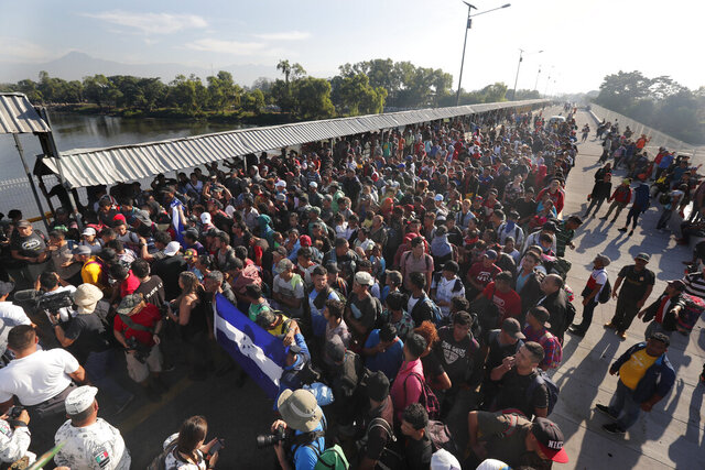 FILE - In this Jan. 18, 2020 file photo, migrants line up behind an Honduran flag at the border crossing between Guatemala and Mexico in Tecun Uman, Guatemala. The European Union said on Thursday, Feb. 13, that it's donating 4 million euros ($4.3 million) to help refugees in Mexico, Costa Rica and Honduras find living-wage jobs and better integrate into society. The announcement in Mexico City on Thursday came as the number of asylum seekers in Mexico in particular has skyrocketed. (AP Photo/Marco Ugarte, File)