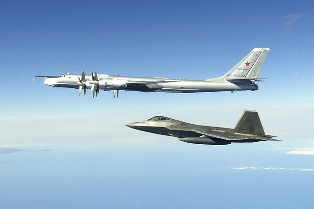 CORRECTS SECOND AND THIRD SENTENCES - In this image taken Tuesday, June 16, 2020,  and released by the North American Aerospace Defense Command, a Russian Tu-95 bomber, top, is intercepted by a U.S. F-22 Raptor fighter off the coast of Alaska. Russian nuclear-capable strategic bombers have flown near Alaska on a mission demonstrating the military's long-range strike capability. The Russian Defense Ministry said that four Tu-95 bombers have flown over the Sea of Okhotsk, the Bering Sea, the Chukchi Sea and the Northern Pacific during an 11-hour mission. The ministry said the bombers were escorted by U.S. F-22 fighters during part of their patrol.  (North American Aerospace Defense Command via AP)