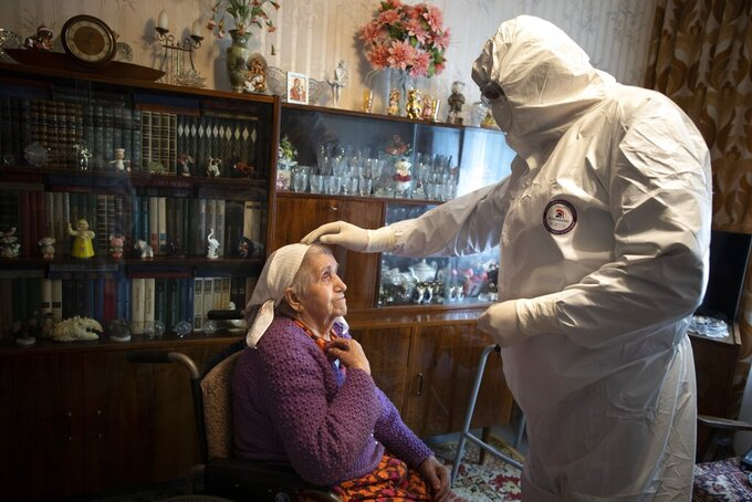 In this photo taken on Tuesday, May 26, 2020, Father Vasily Gelevan, wearing a biohazard suit and gloves to protect against the coronavirus, blesses Tamara Trusova, 90, who is suspected of having coronavirus, at her apartment in Moscow, Russia. In addition to his regular duties as a Russian Orthodox priest, Father Vasily visits people infected with COVID-19 at their homes and hospitals. (AP Photo/Alexander Zemlianichenko)
