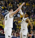 Michigan center Jon Teske (15) and guard Jordan Poole (2) react after a play during the second half of an NCAA college basketball game against Wisconsin, Saturday, Feb. 9, 2019, in Ann Arbor, Mich. Michigan won 61-52. (AP Photo/Carlos Osorio)