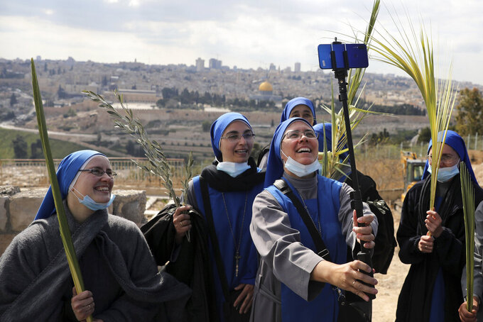 Nuns pose for a selfie as they mark Palm Sunday on the Mount of Olives in Jerusalem, Sunday, March 28, 2021. A year after coronavirus restrictions halted mass gatherings, Christians are celebrating Holy Week together. (AP Photo/Mahmoud Illean)