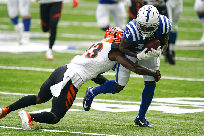 Indianapolis Colts' Zach Pascal (14) is tackled by Cincinnati Bengals' Darius Phillips (23) during the second half of an NFL football game, Sunday, Oct. 18, 2020, in Indianapolis. (AP Photo/Michael Conroy)