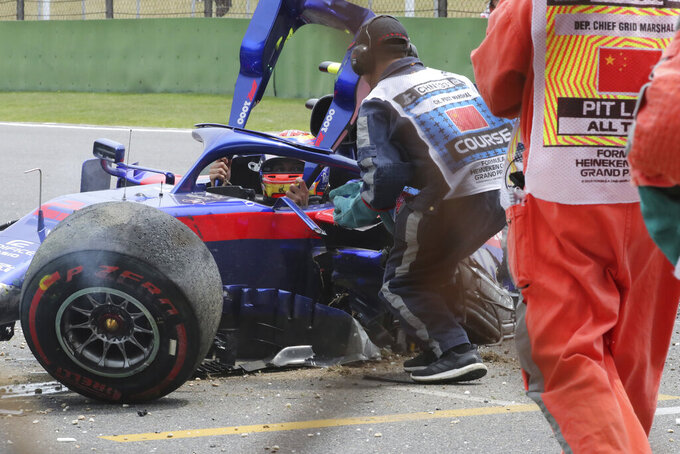 CORRECTS THE NAME OF DRIVER - Toro Rosso driver Alexander Albon of Thailand waits for help to get out of his crashed car during the third practice session for the Chinese Formula One Grand Prix at the Shanghai International Circuit in Shanghai on Saturday, April 13, 2019. (AP Photo/Ng Han Guan)