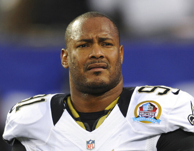 FILE - In this Dec. 9, 2012, file photo, New Orleans Saints defensive end Will Smith appears before an NFL football game against the New York Giants in East Rutherford, N.J. A new retrial date of April 4 was set Wednesday, Oct. 6, 2021, for the man who killed ex-NFL star Will Smith in 2016 following a confrontation over a traffic crash in New Orleans. Cardell Hayes remains free on bond after his earlier manslaughter conviction in Smith's death was overturned because the trial jury verdict was not unanimous. (AP Photo/Bill Kostroun, File)