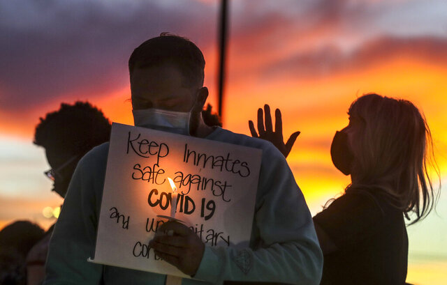 Family members of inmates incarcerated in the Utah Department of Corrections' prison system hold candles and say a prayer following a rally outside the Department of Corrections office in Draper on Tuesday, Oct. 13, 2020.  The families of inmates in the Utah State Prison gathered outside the state Department of Corrections headquarters Tuesday to protest the handling of a coronavirus outbreak at the facility and call for improved safety measures. (Steve Griffin/The Deseret News via AP)