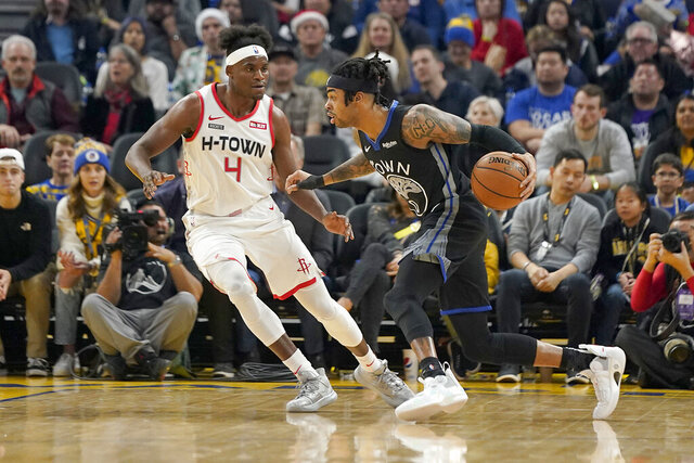 Golden State Warriors guard D'Angelo Russell (0) dribbles past Houston Rockets forward Danuel House Jr. (4) during the first half of an NBA basketball game in San Francisco, Wednesday, Dec. 25, 2019. (AP Photo/Tony Avelar)