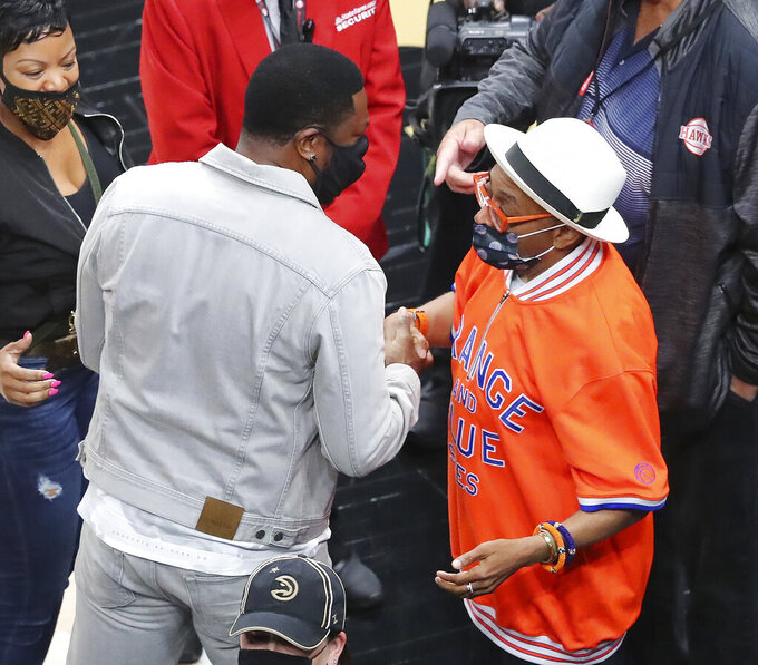 Chris Tucker, front left, and director and actor Spike Lee, right, greet each other while arriving for Game 4 of an NBA basketball first-round playoff series between the Atlanta Hawks and the New York Knicks, Sunday, May 30, 2021, in Atlanta. (Curtis Compton/Atlanta Journal-Constitution via AP)