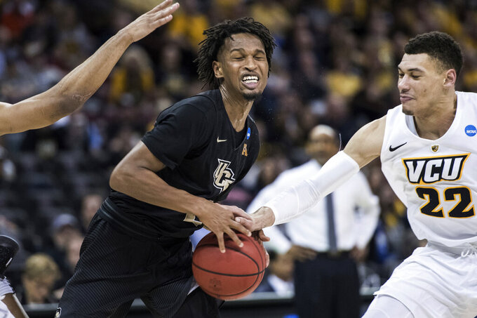 Central Florida guard Terrell Allen (2) has the ball stripped by VCU forward Michael Gilmore (22) during the second half of a first-round game in the NCAA men's college basketball tournament Friday, March 22, 2019, in Columbia, S.C. Central Florida won 73-58. (AP Photo/Sean Rayford)