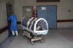 A woman looks out from a coronavirus isolation pod as she is transferred to a special ward for mothers with COVID-19 at the National Perinatal and Maternal Institute in Lima, Peru, Wednesday, July 29, 2020. Better known as the Maternity Hospital, the Institute has dedicated about half its facilities to care for pregnant women infected with the virus. (AP Photo/Rodrigo Abd)