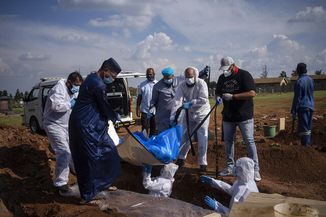 Family members and volunteers from the Saaberie Chishty Society lower the body of a COVID-19 victim into a grave at the Avalon cemetery in Lenasia, South Africa, Monday, Jan. 4, 2021. For more than 30 years, the Saaberie Chishty ambulance service has responded to medical emergencies in a tight-knit Muslim community in Johannesburg. Now, as COVID-19 sweeps through, the service has greatly expanded to offer oxygen and home care. Confronted by an increased number of deaths, it also provides safe body preparation and burial to assure that people are still buried according to Muslim tradition. (AP Photo/Bram Janssen)