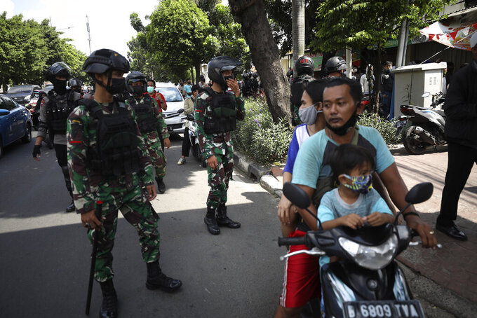 Motorists react as police officers and soldiers disperse a group of people who allegedly plan to stage a rally to support firebrand cleric Rizieq Shihab near the East Jakarta District Court where his sentencing hearing is held in Jakarta, Indonesia, Thursday, May 27, 2021. Judges are scheduled to deliver their verdict on the trial of Shihab, the leader of now-banned Islam Defenders Front, who was accused of inciting people to breach pandemic restrictions by holding events attended by thousands of supporters to commemorate Prophet Muhammad's birthday and the wedding of his daughter in November last year. (AP Photo/Dita Alangkara)
