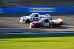 Tate Fogleman (02) and Bryan Dauzat (28) compete during a NASCAR Truck Series auto race at Kansas Speedway in Kansas City, Kan., Friday, July 24, 2020. (AP Photo/Charlie Riedel)