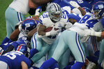 Dallas Cowboys' Ezekiel Elliott, center, pushes through New York Giants defenders to score a touchdown during the second half of an NFL football game, Sunday, Jan. 3, 2021, in East Rutherford, N.J. (AP Photo/Frank Franklin II)