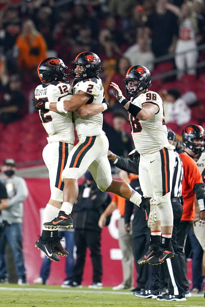 Oregon State linebacker Jack Colletto (12) celebrates his interception with linebacker Andrzej Hughes-Murray (2) and defensive lineman Cody Anderson (98) during the second half of an NCAA college football game against Southern California Saturday, Sept. 25, 2021, in Los Angeles. (AP Photo/Marcio Jose Sanchez)