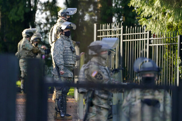 Members of the Washington National Guard stand along a perimeter fence at the Governor's Mansion, Sunday, Jan. 10, 2021, at the Capitol in Olympia, Wash. Washington Gov. Jay Inslee activated members of the National Guard this week to work with the Washington State Patrol to protect the Capitol campus ahead of the state Legislature opening its 2021 legislative session Monday, as several protests and rallies are expected. (AP Photo/Ted S. Warren)