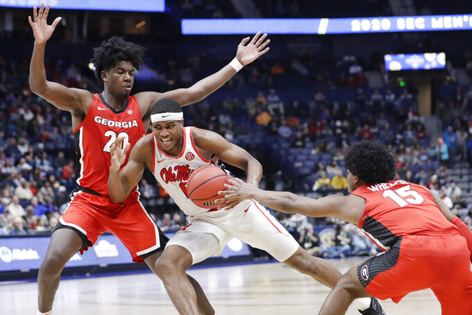 Mississippi's Blake Hinson, center, drives against Georgia's Rayshaun Hammonds (20) and Sahvir Wheeler (15) in the second half of an NCAA college basketball game in the Southeastern Conference Tournament Wednesday, March 11, 2020, in Nashville, Tenn. Georgia won 81-63. (AP Photo/Mark Humphrey)