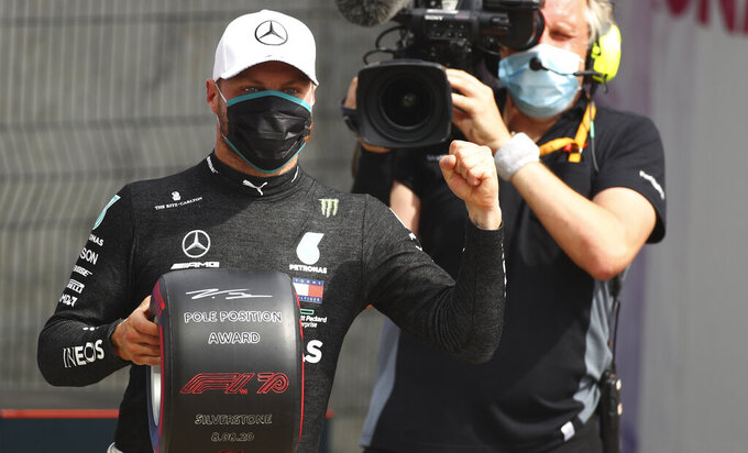 Mercedes driver Valtteri Bottas of Finland jubilates after setting the fastest time during the qualifying session at the 70th Anniversary Formula One Grand Prix at the Silverstone circuit, Silverstone, England, Saturday, Aug. 8, 2020. (Bryn Lennon, Pool Photo via AP)
