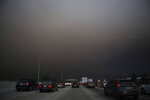 Traffic makes their way south on I-15 as ash from the Holy Fire fills the air on Aug. 9, 2018 in Lake Elsinore, Calif.  More than a thousand firefighters battled to keep a raging Southern California forest fire from reaching foothill neighborhoods Friday before the expected return of blustery winds that drove the flames to new ferocity a day earlier. (AP Photo/Patrick Record)