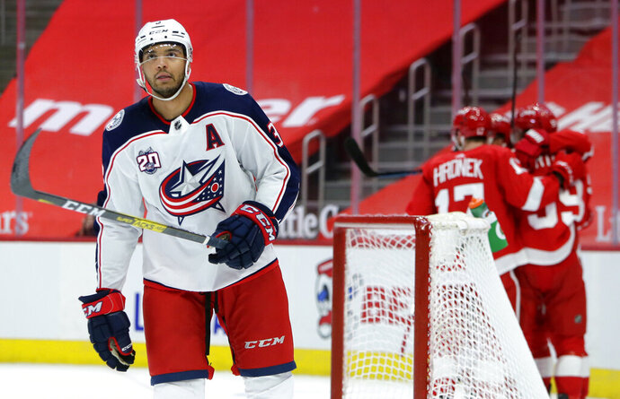 Columbus Blue Jackets defenseman Seth Jones, left, skates away as Detroit Red Wings left wing Tyler Bertuzzi, right, celebrates his game-winning goal with Filip Hronek and other teammates during overtime of an NHL hockey game Tuesday, Jan. 19, 2021, in Detroit. (AP Photo/Duane Burleson)